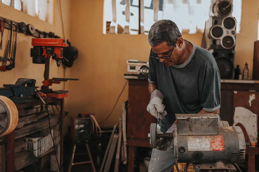 man using bench grinder